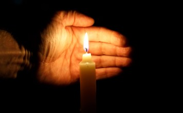 photograph of palm protecting candle at vigil