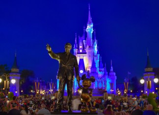 photograph of Walt Disney Statue with Disney Castle in background