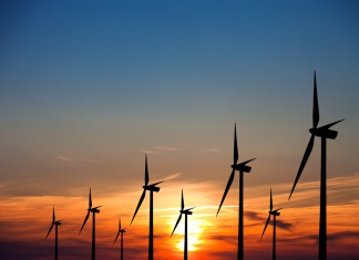 photograph of wind turbines at sunset
