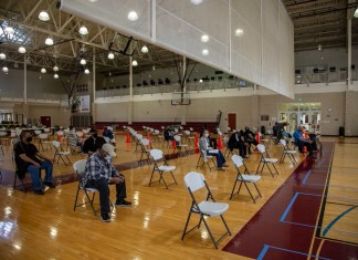 photograph of patients waiting in gym to be vaccinated