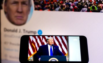 photograph of trump speech playing on phone with Trump's Twitter page displayed in the background