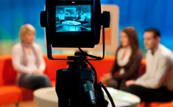 photograph of TV studio with actors displayed in camera viewfinder