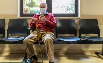 photograph of elderly man masked in waiting room