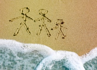 photograph of stick family carved into beach