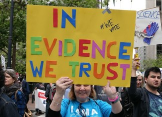 """photograph of """"In Evidence We Trust"""" protest sign"""