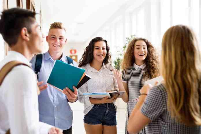 High school teens standing around holding books
