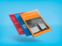 Three spiral bound books in front of a blue background