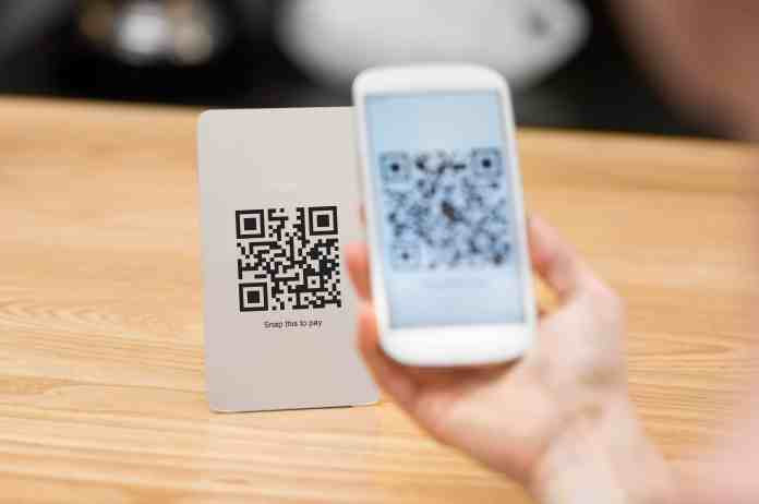 Close up of customer hand making payment through smart phone and scan code