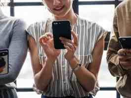 Three people scrolling through their phones.