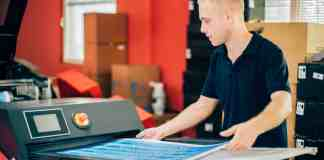 Young man working in printing factory. Man is grabbing prints from the digital printing press