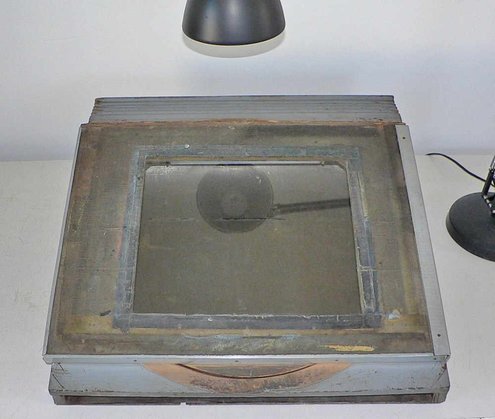 """""""disc"""" covered with linoleum with clear glass taped within the recessed opening"""