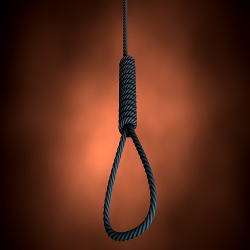 An eerie silhouetted view of a rope made into a hangmans noose on an orange backlit background