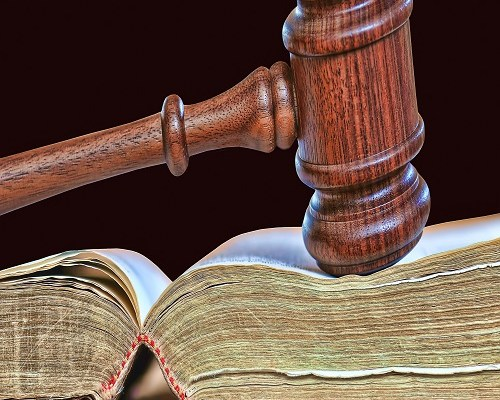 wooden gavel atop old book
