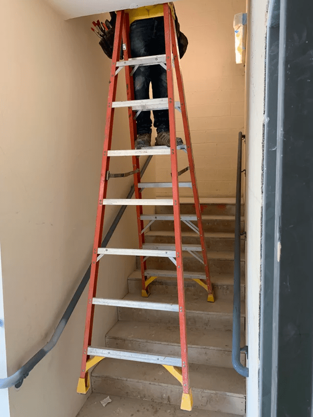 OSHA fail: A man using ladders balanced on a staircase.