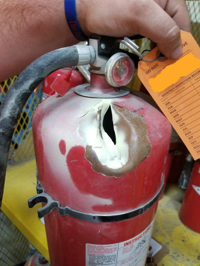 OSHA fail: fire extinguisher with a cut in it.