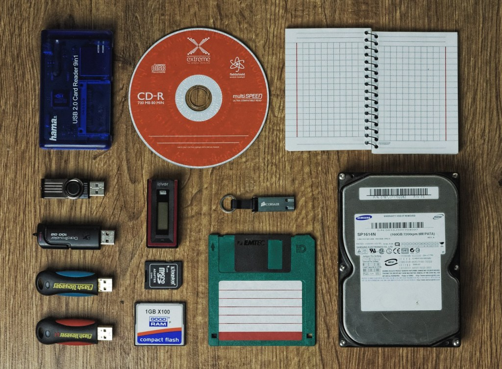 Backups have come a long way. Image depicts old fashioned backup methods. A blue 9 in 1 card reader, red CD-R, small spiral notebook, several USB thumb drives, a green 3.5 inch floppy and a hard drive.