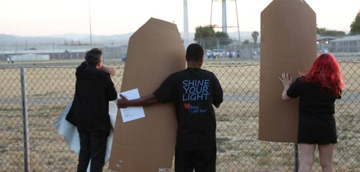 """Three people stand in front of a chain link fence that marks the edge of a prison. All three people face the prison and the central figure wears a shirt with the text """"shine your light."""""""
