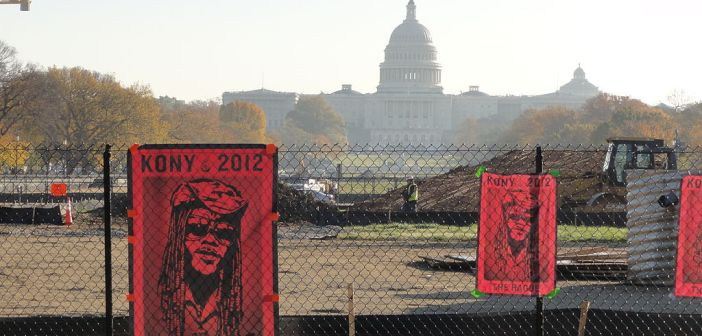 "A photograph displays red posters with the text ""Kony 2012"" and an image of a man who appears to be African and wears a hat, sunglasses, and long hair. The poster appears on a chain link fence with the U.S. Capitol building visible in the background, far behind the fence."