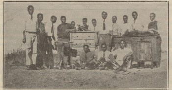 This image shows a group of men who appear to be African standing with several pieces of furniture. Some hold carpentry tools.