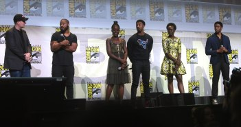 A photograph shows the cast of the movie Black Panther standing on a stage, holding microphones, and appearing to answer questions. The backdrop of the stage notes San Diego Comic Con.