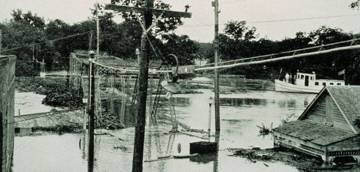 A black and white photograph shows a flooded area that includes a bridge, a house, and a boat. Water reaches almost to the roof of the house and covers the bottom of the bridge.