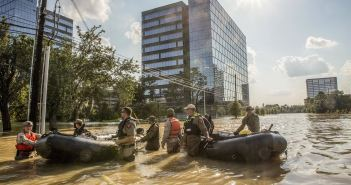 A photograph shows two groups of men in uniforms standing in waist-high water next to rubber boats. They appear in front of large office buildings in what appears to be a flooded street.
