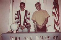 A color photograph shows two young men standing in front of a table. On the table appears a globe and two action figures in soldier's uniforms.