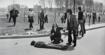 A black and white photograph shows a young woman in distressing knelling on the ground next to what appears to be a dead body. Several other people stand near her and also look at the body.