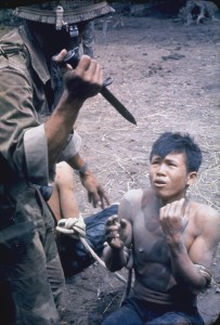 A color photograph shows a soldier standing above a man sitting on the ground. The soldier holds a knife and the seated man appears frightened.