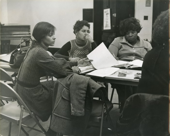 A black and white photograph shows several women sitting around a table with open binders and pieces of paper on the table.
