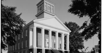 A photograph shows the front of a large building with multiple columns and a bell tower.