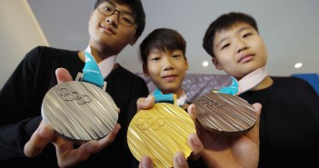 A photograph shows three young people holding a silver, gold, and bronze medal.