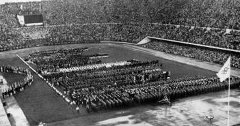 An image shows many rows of people standing in the middle of a large stadium.