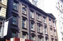 A photograph displays the facade of a large brown building on a city street.