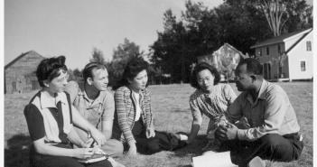 Five students of different races converse on a grassy field.