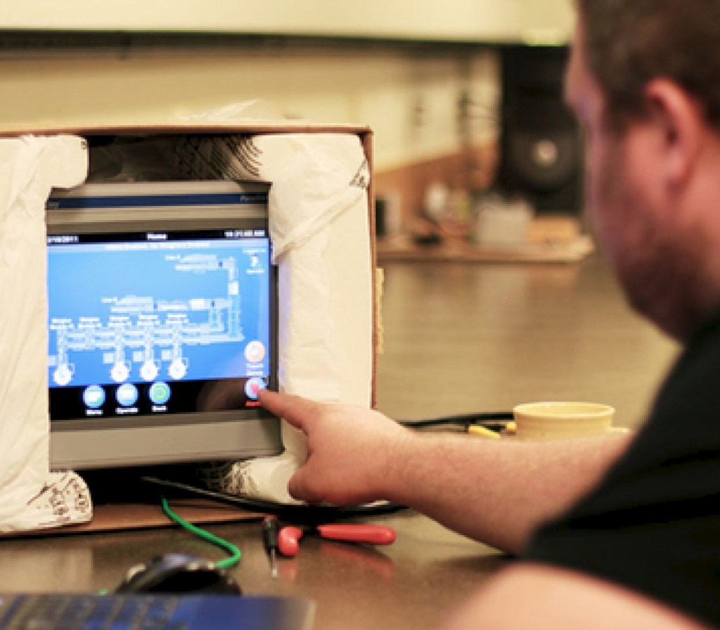 Process Solutions engineer programming scada software on an HMI screen
