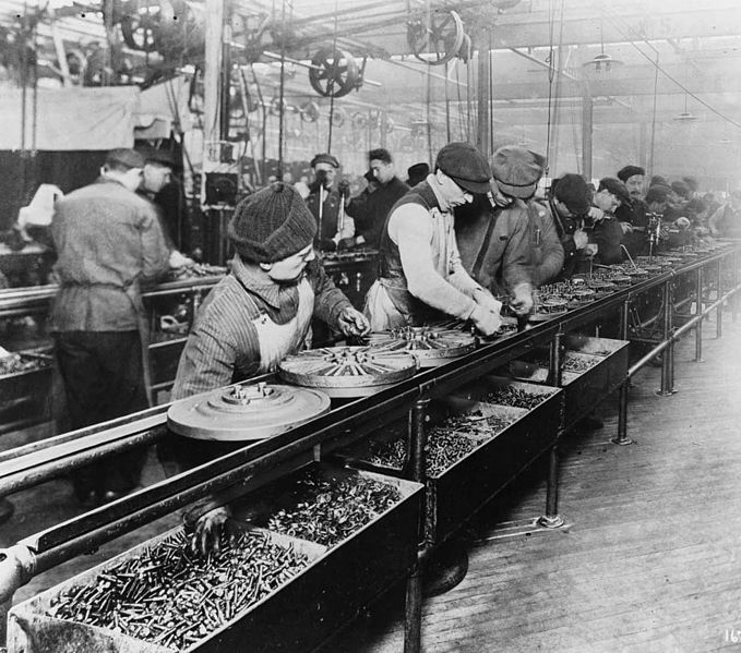 Workers on the first moving assembly line put together magnetos and flywheels for 1913 Ford autos. Image via Wikimedia Commons / CC0 1.0