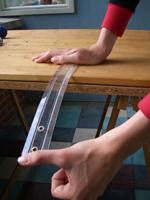 trek kort het uiteinde van de liniaal dat uitsteekt naar beneden, zodat de liniaal gaat trillen