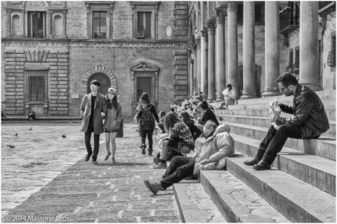Firenze: persone sedute sulle scalinate di piazza Santissima Annunziata si godono il stepore del sole invernale, qualcuno mangia, qualcuno si appisola. Una giovane coppia orientale passeggia.