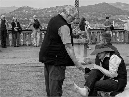 Dopo la salita a Piazzale Michelangelo un'anziana turista si massaggia i piedi stanchi