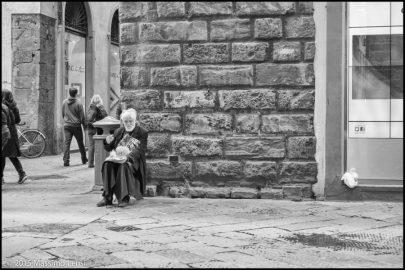 Anziano signore seduto con in braccio un piccolo cane chiede l'elemosina in via del Corso a Firenze,