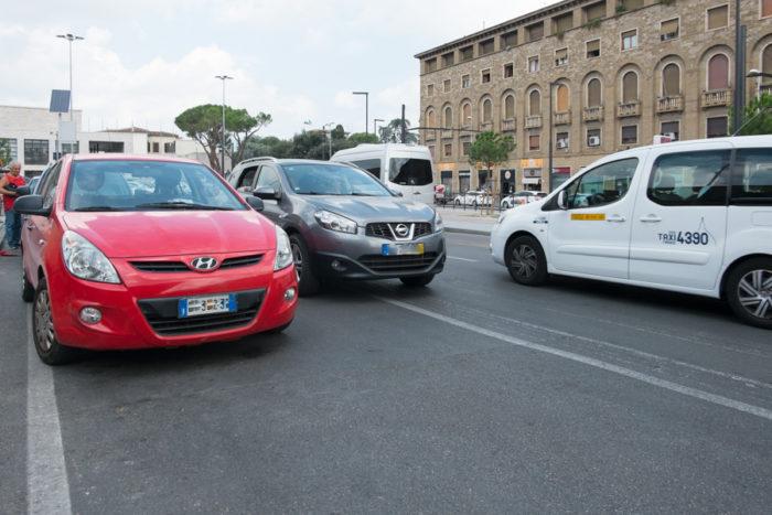 A causa delle auto parcheggiate, l'auto grigia è costretta a invadere la carreggiata opposta e a rischiare scontri con le auto che sopraggiungono. La foto è del 10 agosto 2018, quando il traffico è notevolmente diminuito e i residenti sono in vacanza.