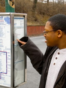 Young student reading a bus schedule