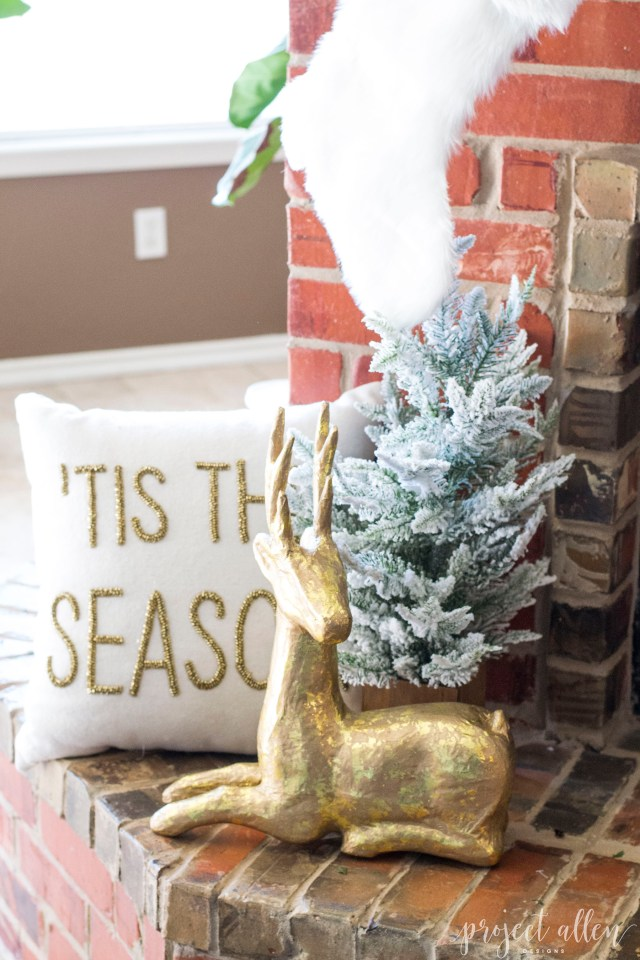 Brick Christmas fireplace with styled mantle and faux gold reindeer.
