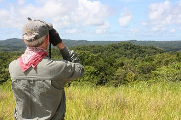 pat scannon surveying the area with binoculars in palau