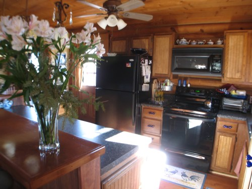 Log Cabin Kitchen Before & After: Black Appliances with repaired cabinets. Cobalt glass hardware.