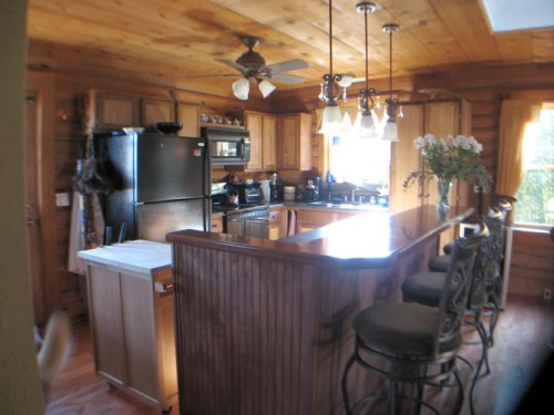 Log Cabin Kitchen Before & After: Work in Process, The log cabin kitchen with repaired cabinets, new appliances and the bar