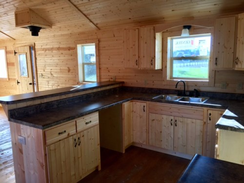 Kitchen with Breakfast Bar - Flu is ready to add a wood stove. – Project Small House in White Tail Log Cabin