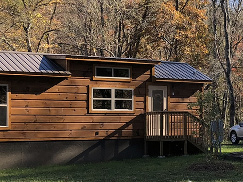 Park Model Log Cabin with a brown metal roof - Open House at Acony Bell Tiny Home Village – Tiny Log Cabins at Acony Bell Tiny Home Village - Project Small House