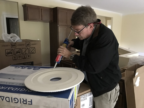 Putting liquid nails on the ceiling medallion for the dining room - Ceiling Medallions in the Dining Room and Entry – Project Small House